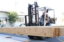 フォークリフトで木材を運ぶ 写真